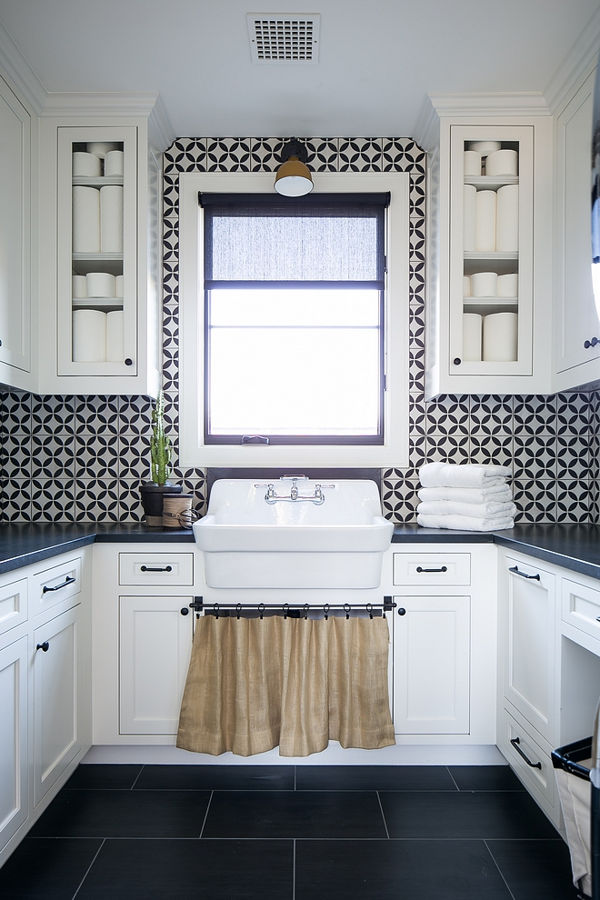 Black and white laundry room featuring white shaker cabinets, black countertop, black and white cement tile and an utility sink Black and white laundry room Black and white laundry room #Blackandwhitelaundryroom #laundryroom