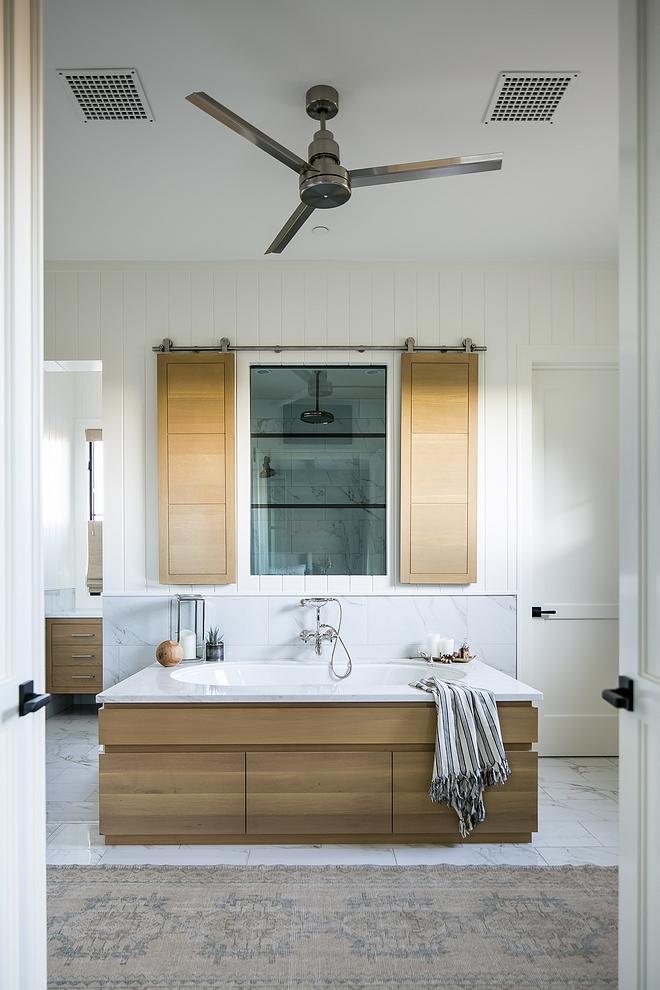 Bathroom featuring White Oak tub surround and shower White Oak shutters hung in barn door hardware #WhiteOak #tubsurround #bathroom