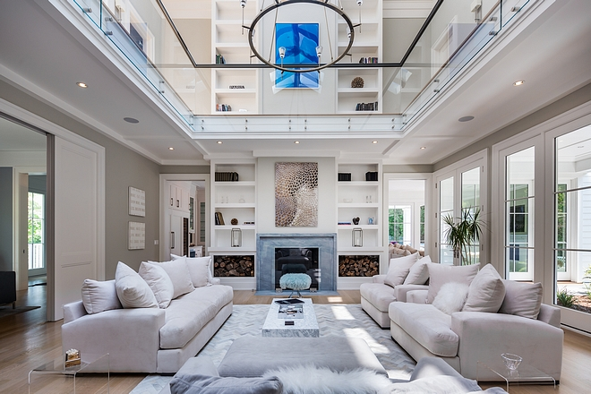 Two-story fireplace A grand two-story fireplace flanked by towering bookcases anchors the room as it shoots into the second floor #twostoryfireplace #fireplace #bookcase