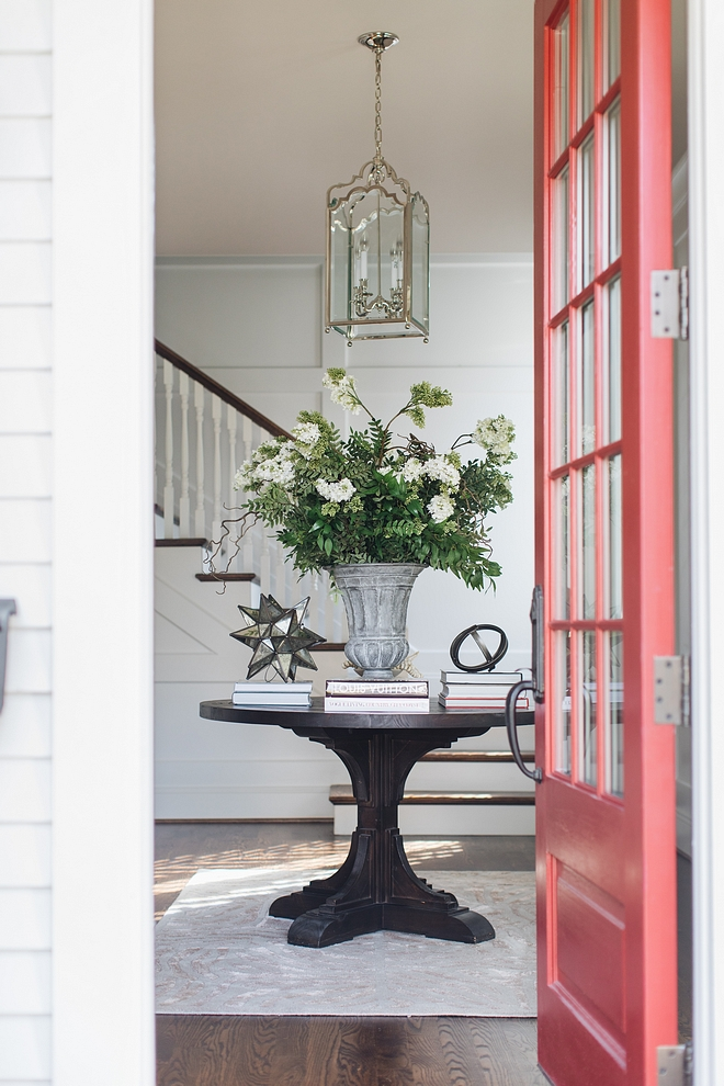 Classic foyer with round table, neutral rug and grid board and batten wainscoting painted in Benjamin Moore Decorator White #foyer #gridboardandbetten #wainscoting #BenjaminMooreDecoratorWhite