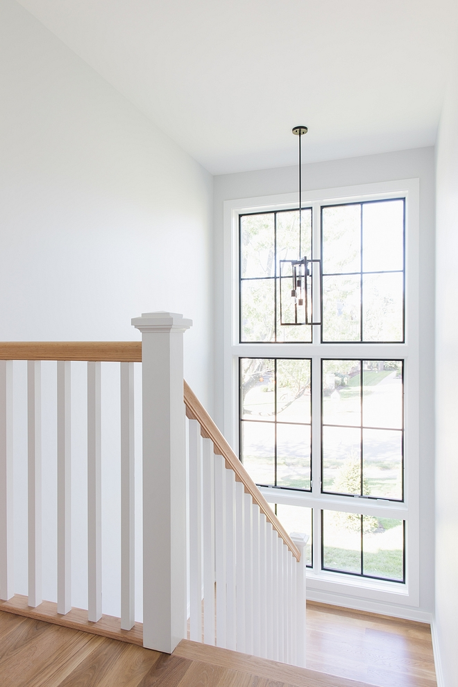 Floor-to-ceiling windows bring plenty of natural light to this stairway Wall paint color is Sherwin Williams Site White #stairway #windows #paintcolor