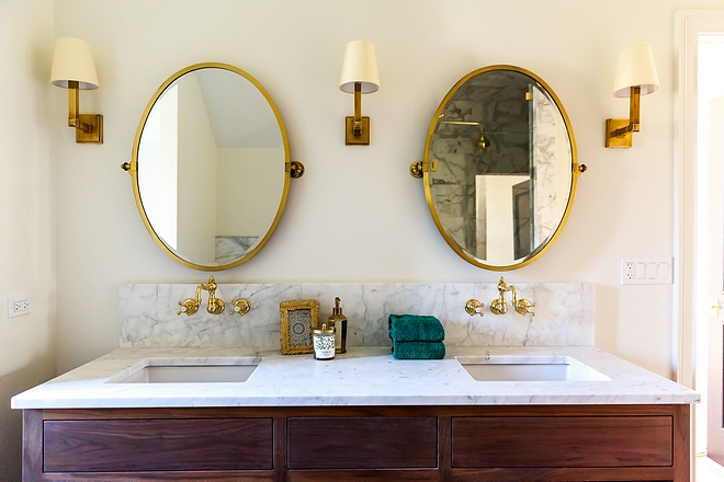 Bathroom Brass Mirror Bathroom with oval brass mirrors over brass mounted faucets, Waterworks Julia Wall Mounted Faucet #bathroom #brassmirror #bathroomirror #ovalmirror