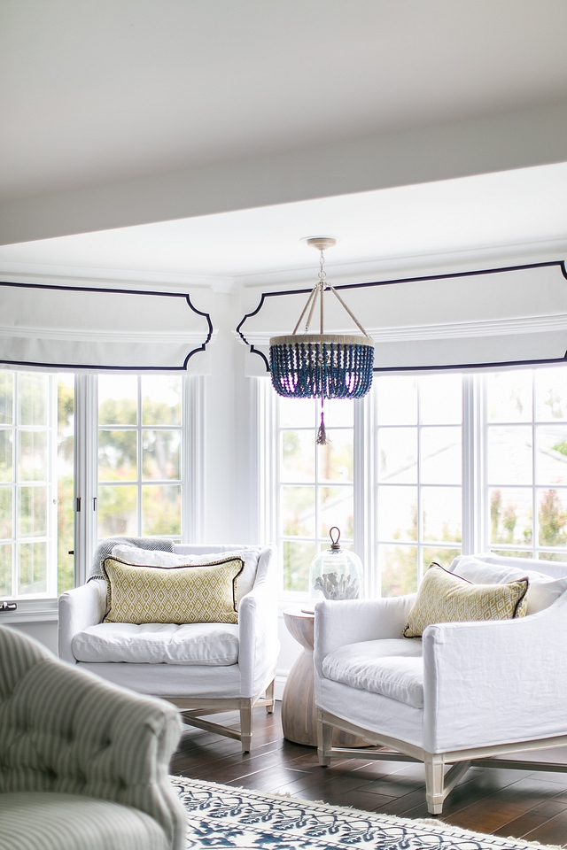 Bedroom sitting area with relaxed white linen chairs and navy agate bead chandelier and white Roman Shades with blue trim #sittingarea #bedroom #chairs #beadchandelier #Romanshades