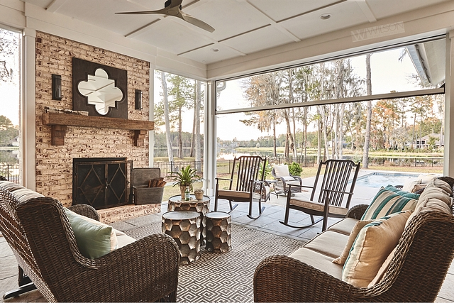 Bi-fold patio doors open to a beautiful screened porch with brick fireplace and coffered ceiling #Bifoldpatiodoor #screenedporch #brickfireplace #cofferedceiling