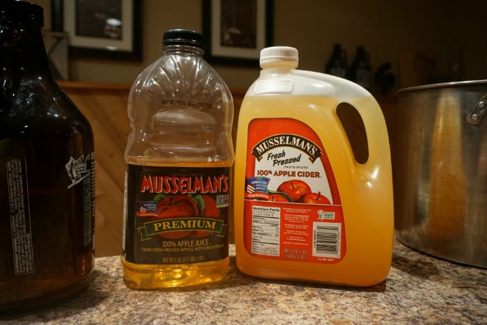 two bottles of apple cider sitting on a table top