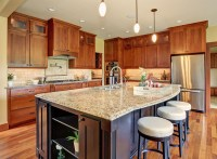 Contemporary kitchen with light granite counters dark wood ...