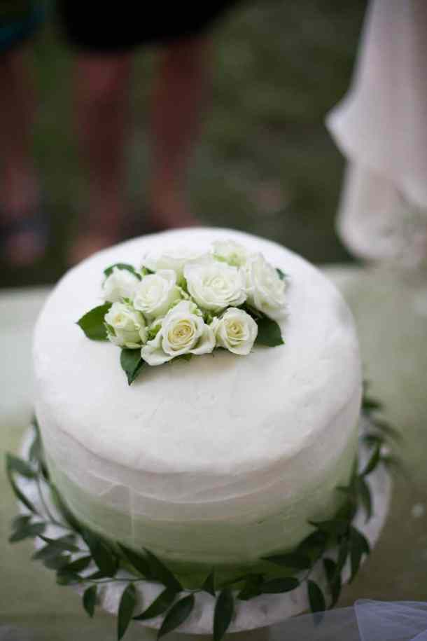 green and white garden wedding cake decorated with dark green foliage and tiny white roses