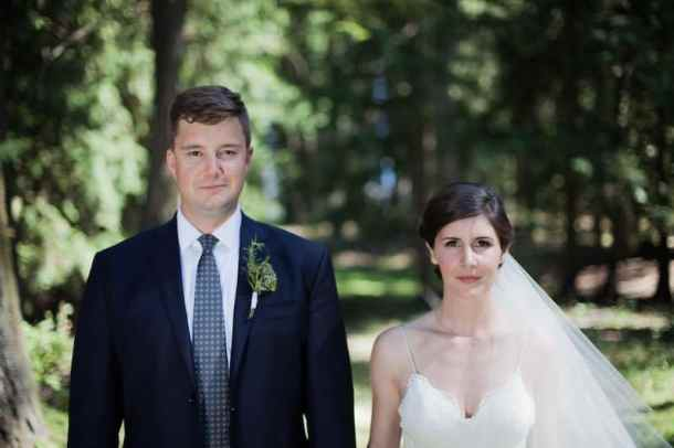 woodsy wedding photo of bride and groom with evergreen forest behind them