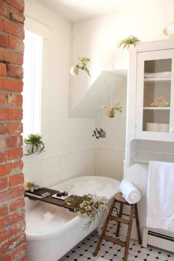 DIY spa day in a white bathroom with antique white tub, brick chimney, and houseplants