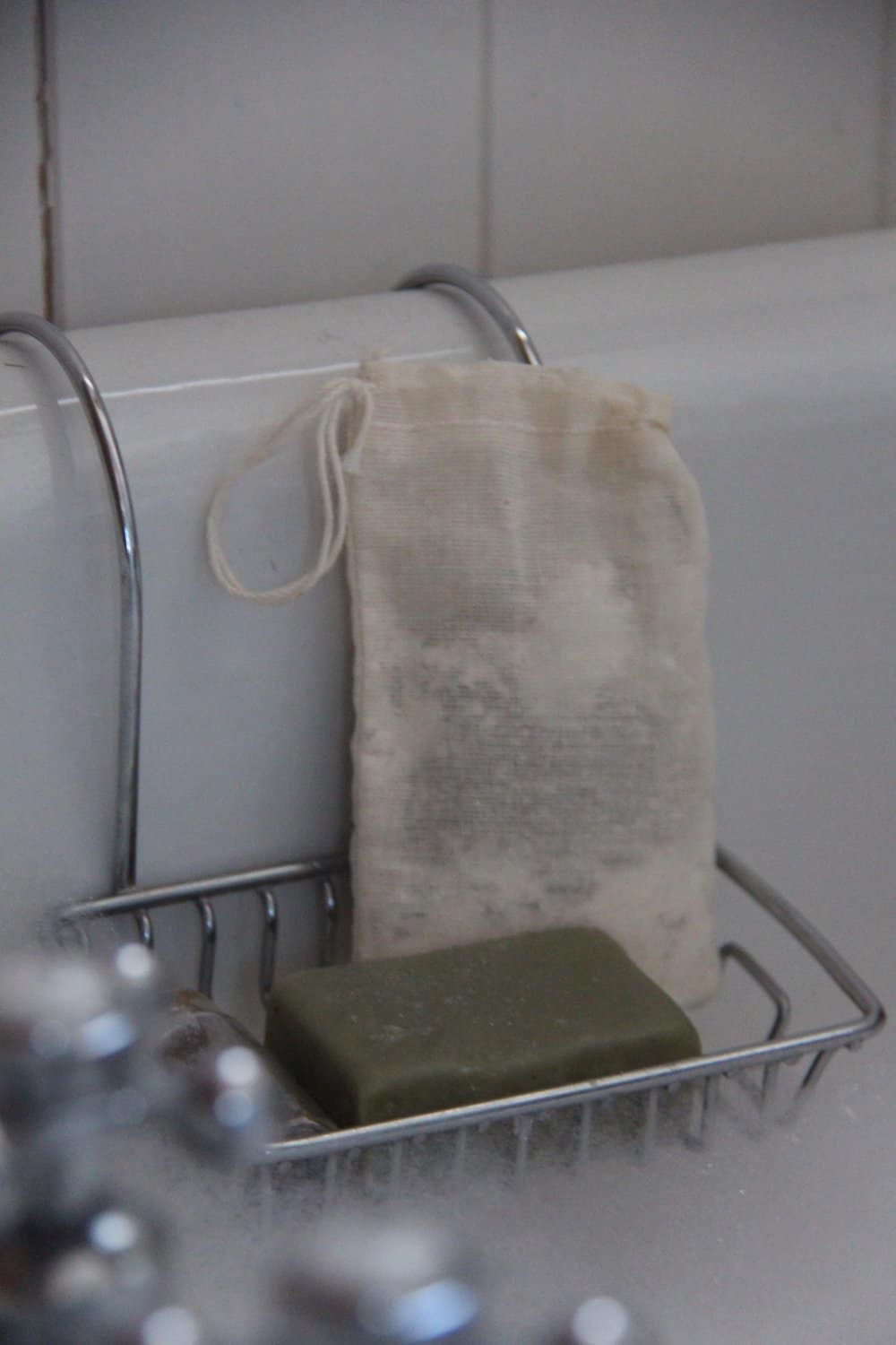 White antique tub edge with silver faucets and soap dish with green bar of soap and fabric tea bag of tub tea