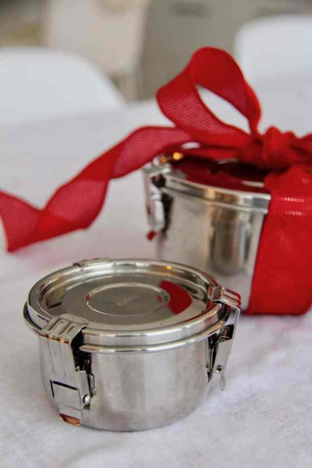 Two round metal food containers, one with a red bow