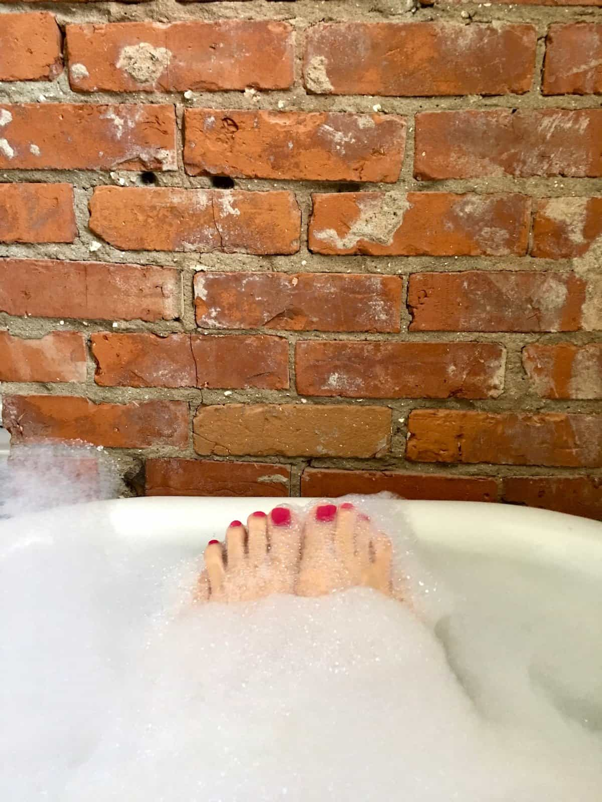 Bubble bath edge with soapy toes peeking out against a background of a brick chimney
