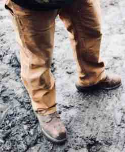 carhartt work pants worn with work boots in the mud on a rainy workday