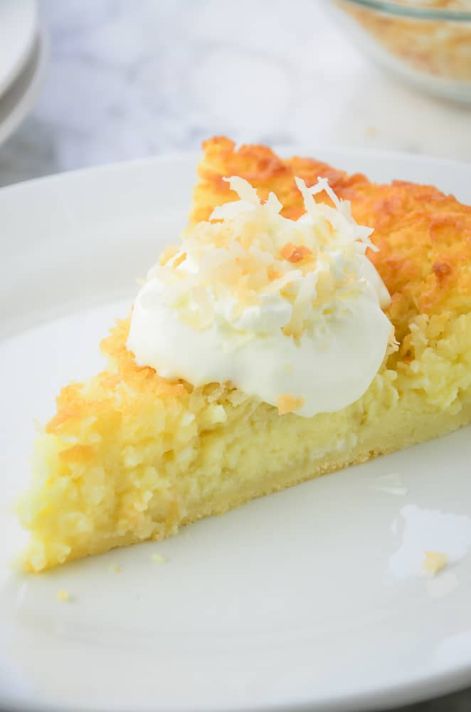 Impossible coconut pie topped with whipped cream and toasted coconut