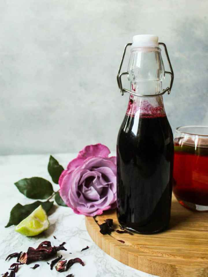 Spiced hibiscus sorrel syrup in a bottle with a rose