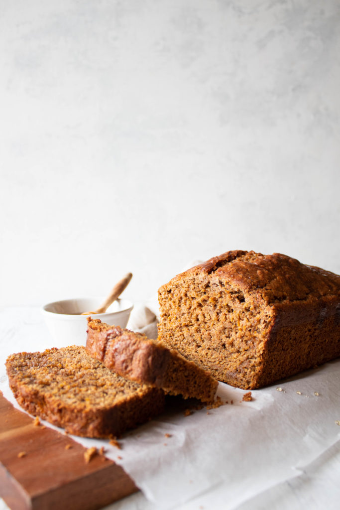 Eye-level picture of carrot cake loaf on wooden board