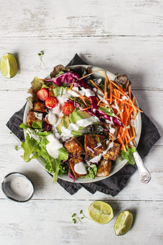 Jerk tofu in a bowl with salad and a coconut yogurt dressing