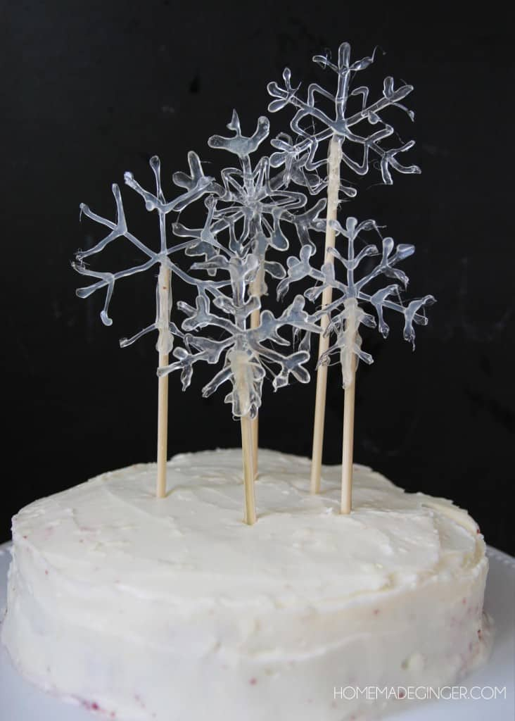 Make some snowflake cake toppers using hot glue. This will make a beautiful DIY cake decoration for any winter occasion!