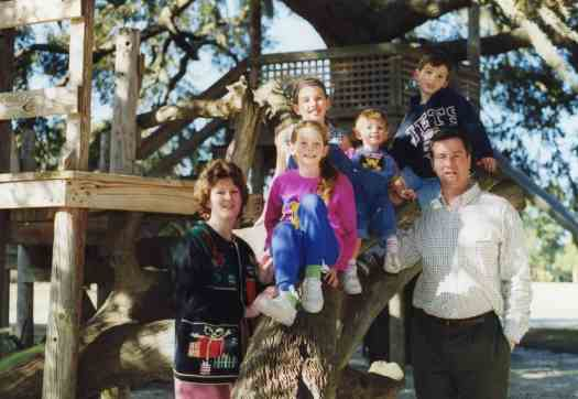 Picture of husband, mom and four children near playground equipment