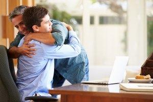 Father hugging son at desk