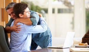 Happy homeschooling father hugging son