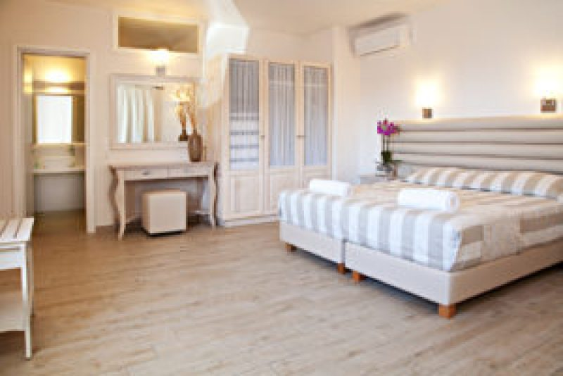 This master bedroom has light wood floors and matching light wood bedroom furniture.