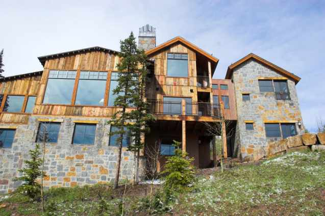 Wood exterior and stone exterior ski chalet on steep slope with huge picture windows.