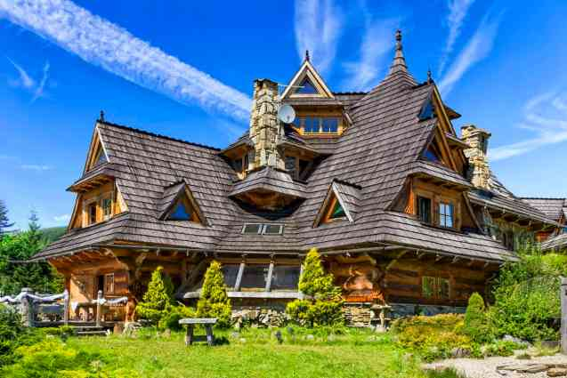 Country log mansion rising up 4 stories with huge sloping cedar shake roof shingles. Intricate detail. Incredible design.