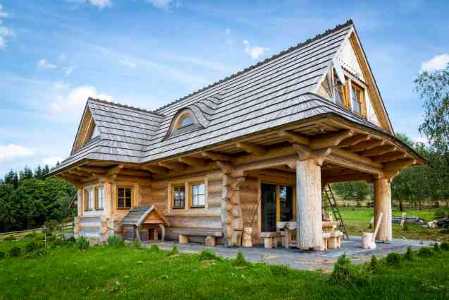 Interesting off-white log home with long wing and ends supported with massive log beams.