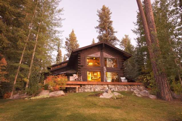 Rustic dark log cabin on stone foundation among towering evergreen trees.