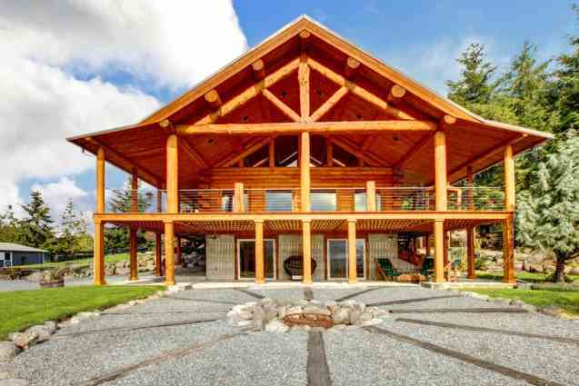 Imposing A-frame style log home with massive chalet style overhang roof and large upper wrap-around deck.
