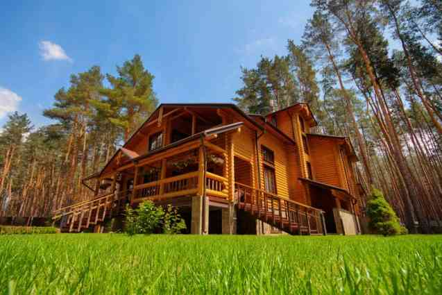Grand log home set among towering evergreen trees. Great elevated front porch.