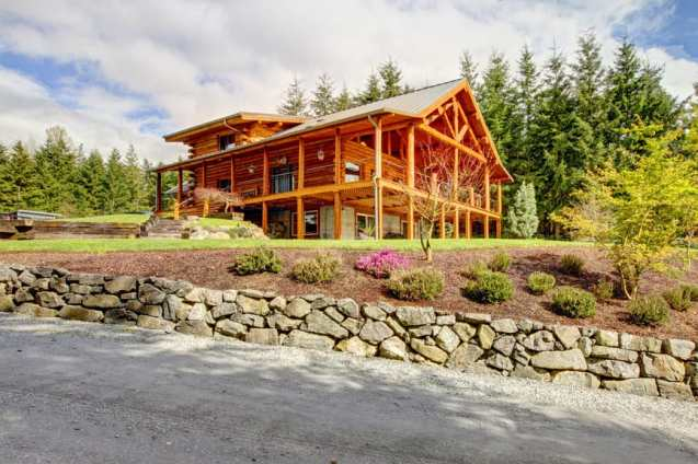 Massive log home with many supporting beams on perimeter of wrap-around deck.