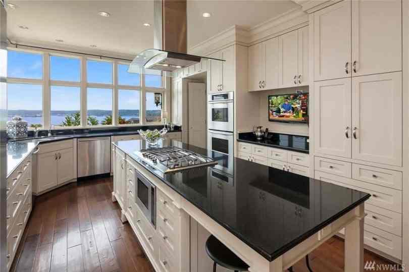 Beige kitchen with black countertops.