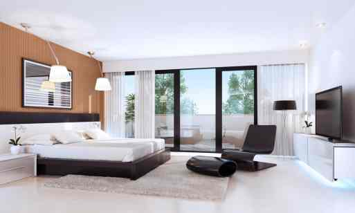 Cool modern bedroom with floating TV stand, modern black chair with ottoman and large platform bed.