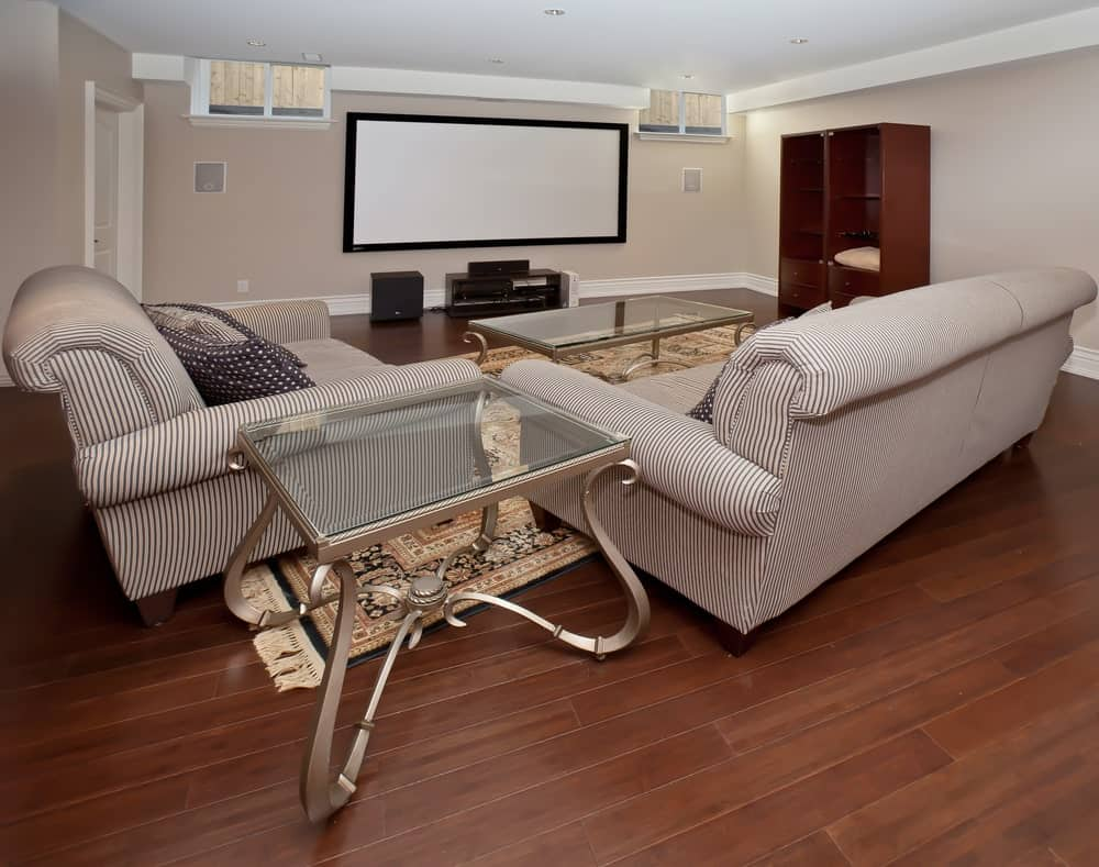 hight resolution of large home theater featuring cozy sofa set on top of the hardwood flooring