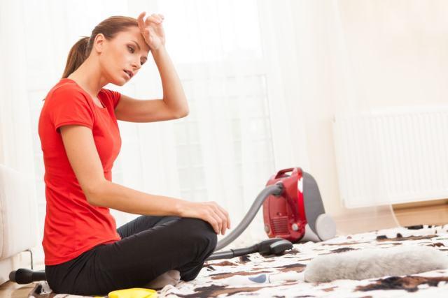 Halıyı temizlemekten yorgun bir kadın.