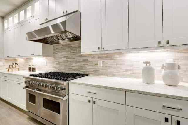 Bu, staonless çelik aletlerin öne çıkmasını sağlamak için duvarları kaplayan beyaz mutfak dolaplarına sahip bir mutfak.