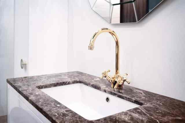 Siyah mermer tezgah ve altın köprü musluklu bir banyo lavabosu.