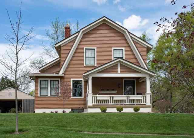 Bu, bir sundurma ve bir gambrel çatısı ile kahverengi evin önüne dışarıdan bir bakış.