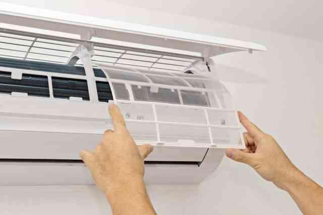 Duvar tipi split klimanın filtrelerini değiştirme sürecinde olan bir adam.