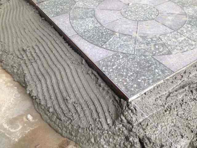 Bir parça granit karo döşeniyor.