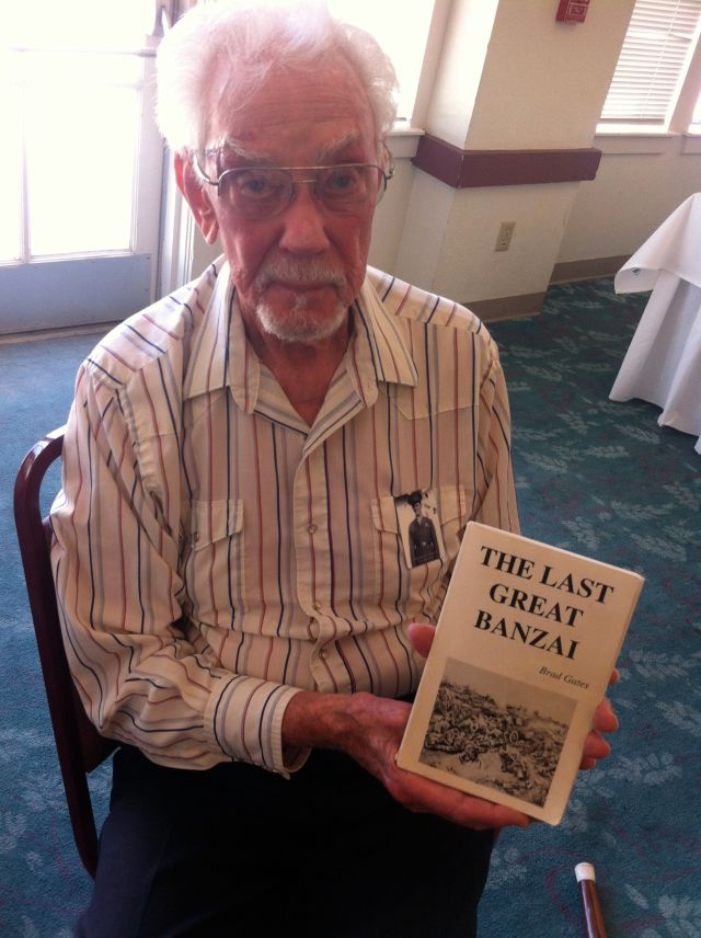 Ken Miller with a book about the banzai charge he survived on Saipan.