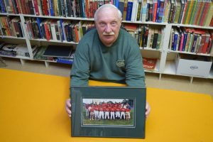 Perth Fastball tournament organizer Neil Fennell holds a framed photo of the New Zealand national team.