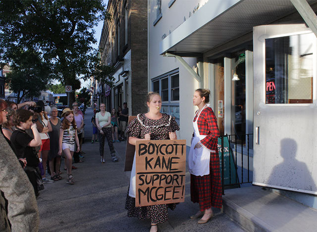 """Play: Woman walking with cardboard sign that says """"Boycott Kane - Support McGee!""""."""