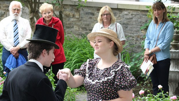 Guy in tophat taking the hand of woman.