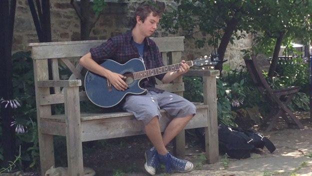 Austin Ritz playing guitar on a bench