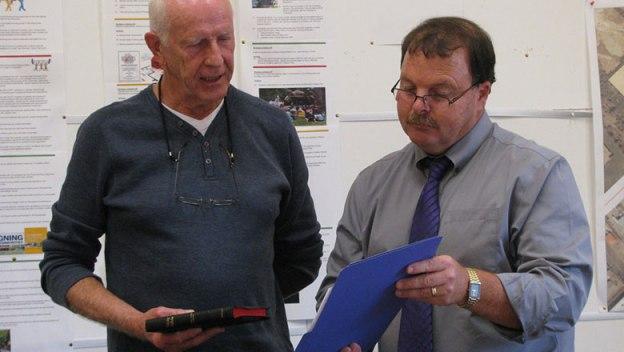 Eric Halpin holding a bible reading from the folder John deRosenroll is holding.