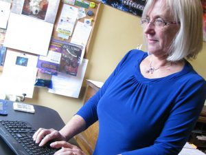 Julie Czerneda standing and typing her books on a computer.
