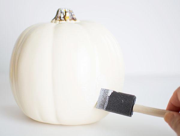 Applying Mod Podge to pumpkin